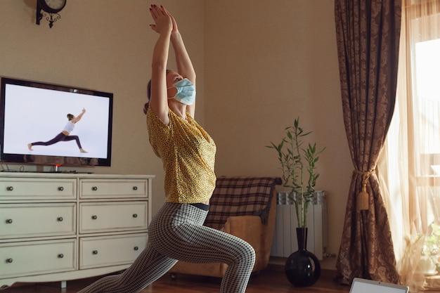 Mujer joven deportiva que toma lecciones de yoga en línea y practica en casa mientras está en cuarentena.