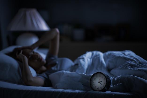 Mujer joven deprimida acostada en la cama no puede dormir por insomnio