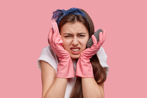 Mujer joven deprimida ocupada mantiene las manos cerca de las mejillas, lleva esponjas, mira la habitación desordenada, tiene que ordenar todas las cosas