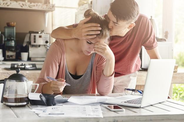 Mujer joven deprimida que sostiene la pluma, calculando el presupuesto familiar