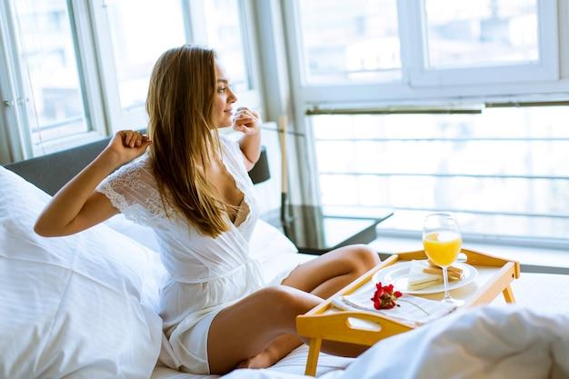 Mujer joven desayunando en la cama en el dormitorio