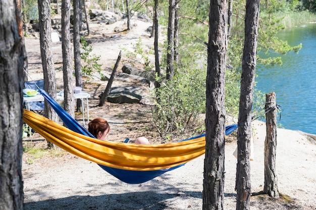 Mujer joven descansa en una hamaca entre los pinos en el lago en un caluroso día de verano