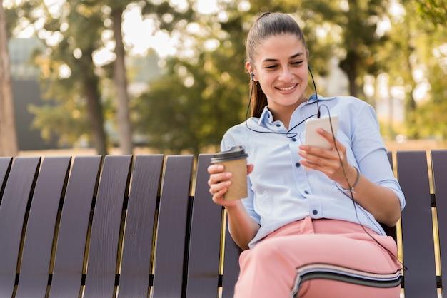 La mujer joven descansa en el parque del otoño en el banco después de un paseo y escucha la música en el teléfono.