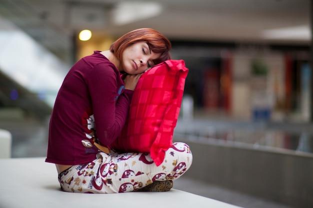 Mujer joven descansando con un cojín rojo