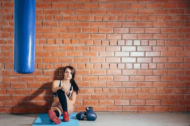 Mujer joven descansando después de un entrenamiento en el gimnasio