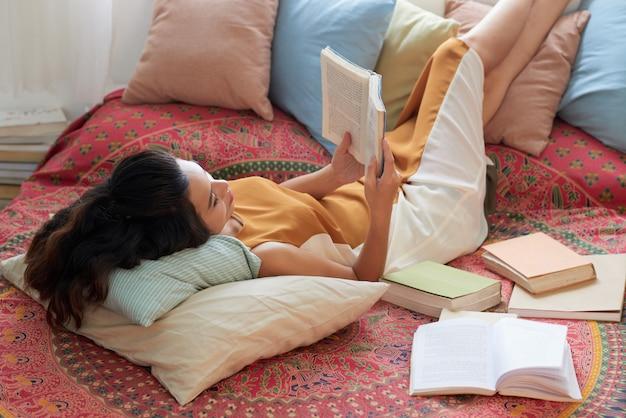 Mujer joven descansando con el libro en la cama con las piernas sobre las almohadas