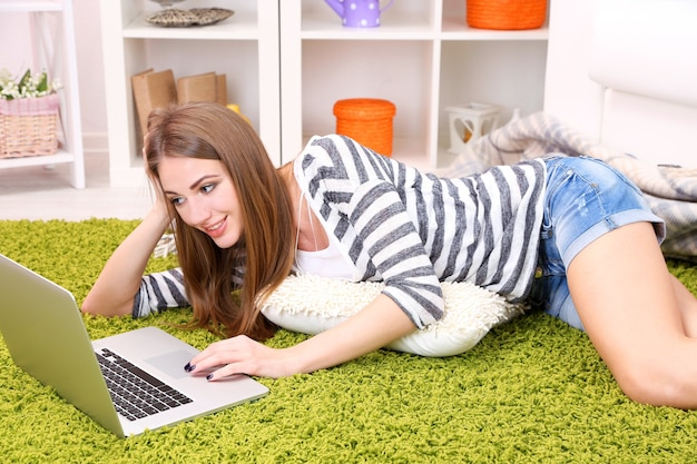 Mujer joven descansando con el portátil en el piso cerca del sofá, en casa