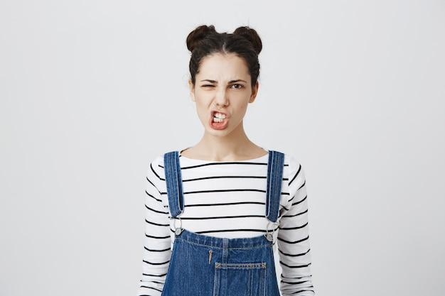 Mujer joven descarada apretar los dientes, haciendo muecas