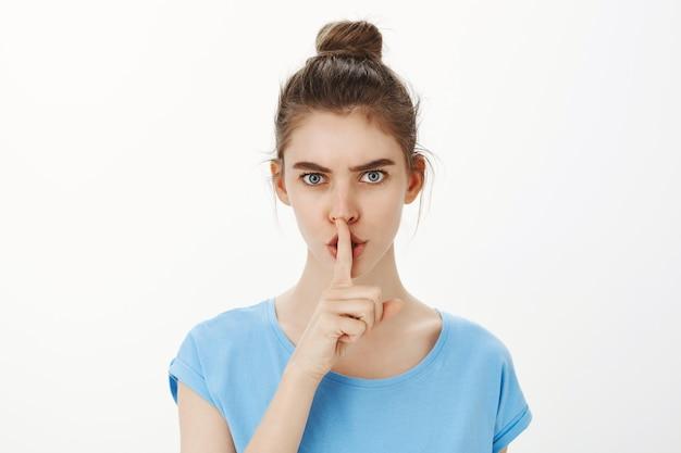 Mujer joven descarada shhh hacia ti, callando con el dedo presionado en los labios