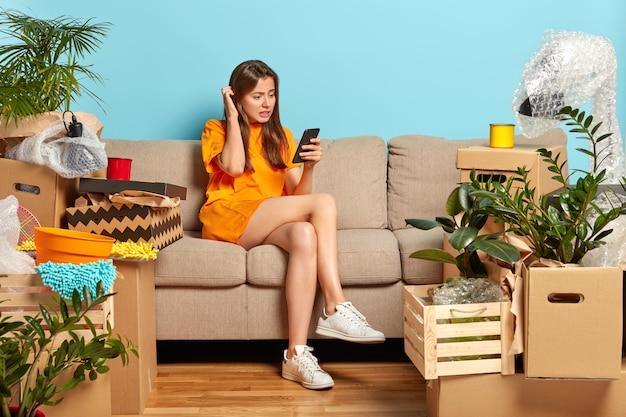 Mujer joven desconcertada se rasca la cabeza, intenta pagar el piso en línea, no puede realizar el pago