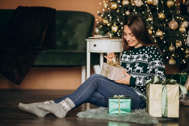 Mujer joven desempacando el regalo de navidad junto al árbol de navidad