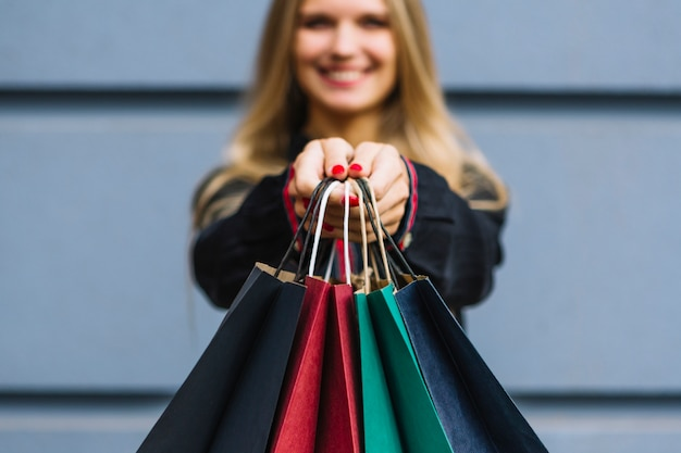 Mujer joven de desenfoque mostrando coloridos bolsos de compras
