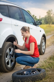 Mujer joven desenroscando las tuercas de la rueda plana del coche en el campo