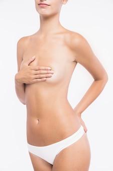 Mujer joven desnuda con la mano en el pecho