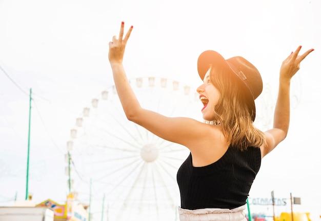 Mujer joven despreocupada que muestra el signo de la paz en el parque de atracciones