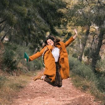 Mujer joven despreocupada que sostiene el libro en la mano que salta en rastro de montaña