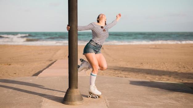 Mujer joven despreocupada que sostiene el pilar que se coloca delante de la playa