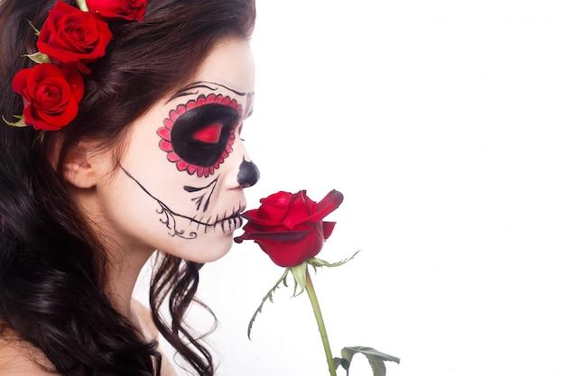 Mujer joven en el día de los muertos máscara cráneo arte cara y rosa