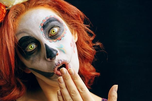 Una mujer joven en el día de los muertos máscara cráneo cara arte.
