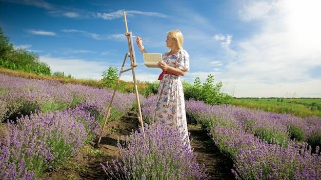 Mujer joven dibujo imagen de hermoso campo de lavanda en la provenza.