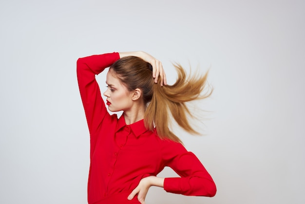 Mujer joven de diferentes emociones en ropa roja en un espacio de luz