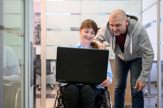 Mujer joven con discapacidad en el cargo con un compañero de trabajo