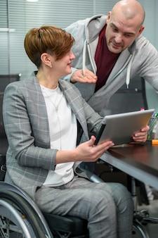 Mujer joven con discapacidad en la oficina escuchando