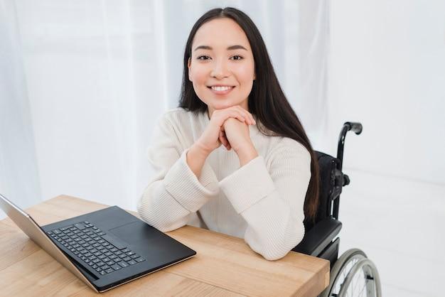 Mujer joven discapacitada alegre que se sienta en la silla de ruedas que mira la cámara con el ordenador portátil en la tabla de madera