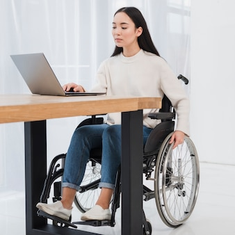 Mujer joven discapacitada sentada en silla de ruedas usando laptop