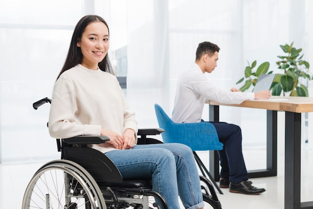 Mujer joven discapacitada sonriente que se sienta en la silla de ruedas que mira la cámara delante del hombre que trabaja en el ordenador portátil