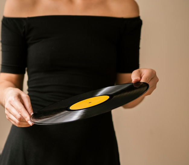 Mujer joven con disco de vinilo con ambas manos