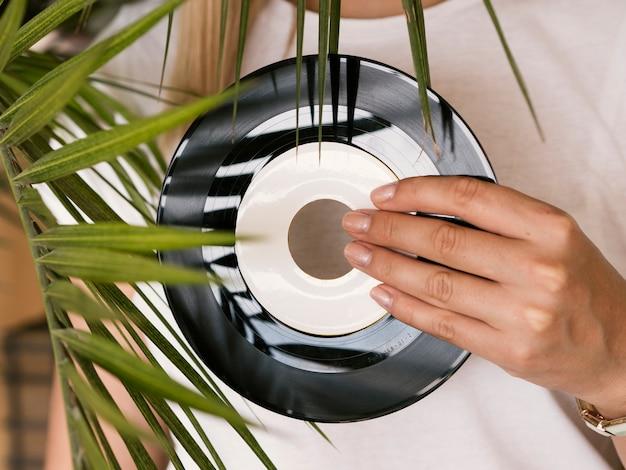 Mujer joven con disco de vinilo retro cerca de la planta