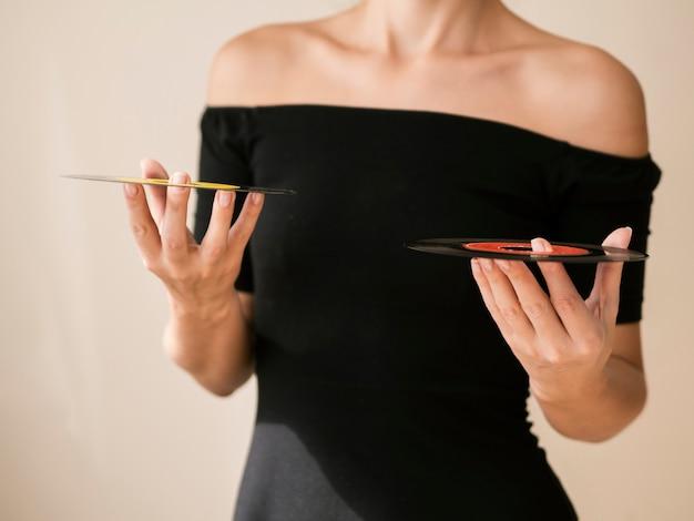 Mujer joven con discos de vinilo en ambas manos