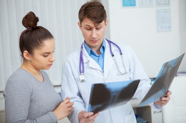 Mujer joven discutiendo sus radiografías con el médico en el hospital