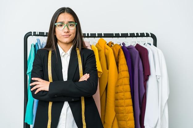 Mujer joven diseñador asiática aislada en la pared blanca infeliz mirando a puerta cerrada con expresión sarcástica.