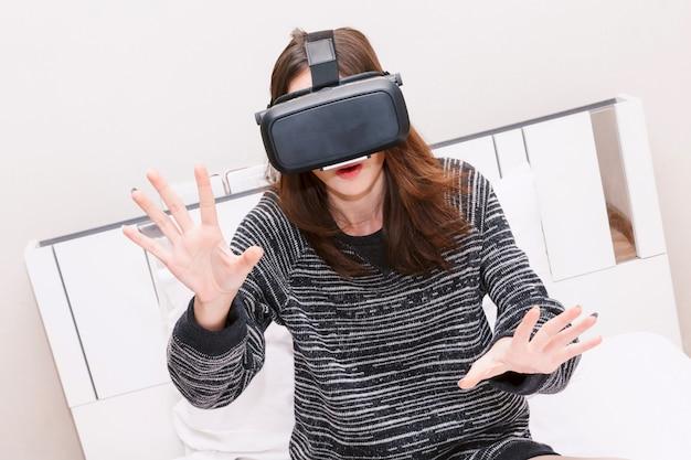 Mujer joven disfruta con gafas de realidad virtual en casa.