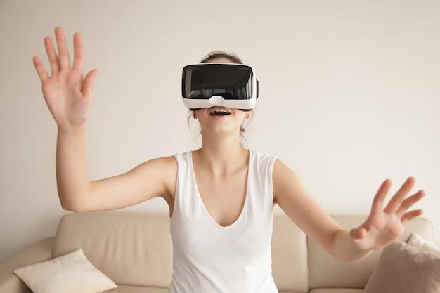 Mujer joven disfruta de juegos de realidad virtual en el sofá en casa