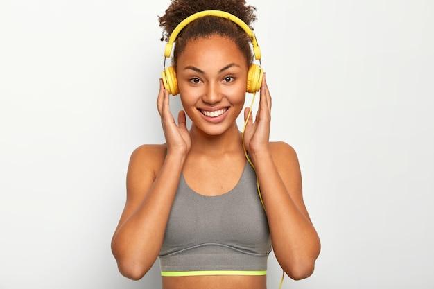 Mujer joven disfruta de la música como motivación personal, mantiene ambas manos en los auriculares, sonríe agradablemente, usa sujetador deportivo gris