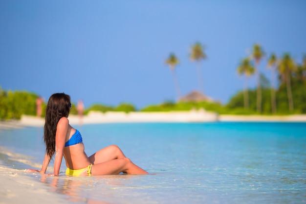 Mujer joven disfruta de vacaciones en la playa tropical