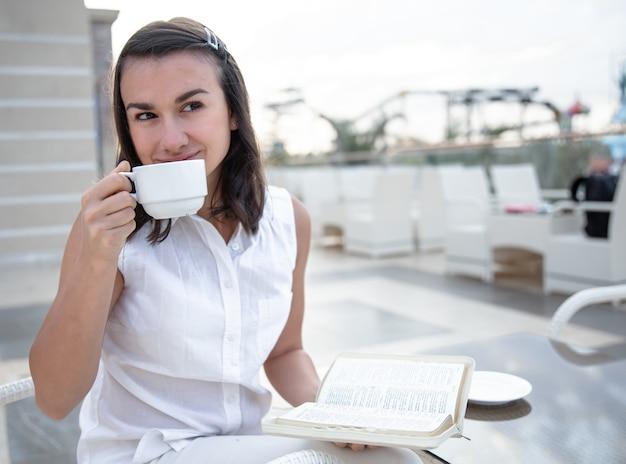 Mujer joven disfrutando del café de la mañana en una terraza de verano abierta con un libro en sus manos