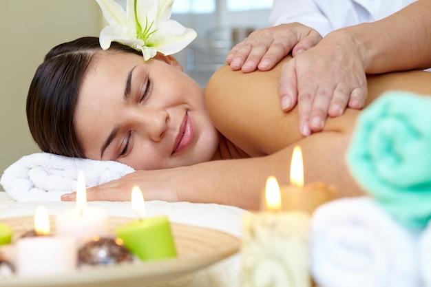 Mujer joven disfrutando de un masaje de hombros
