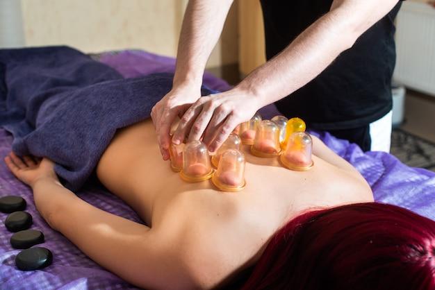Mujer joven disfrutando de masaje de espalda con ventosas en spa. las manos del médico varón ponen latas de plástico al vacío. relajación, belleza, concepto de tratamiento corporal. masaje a domicilio.