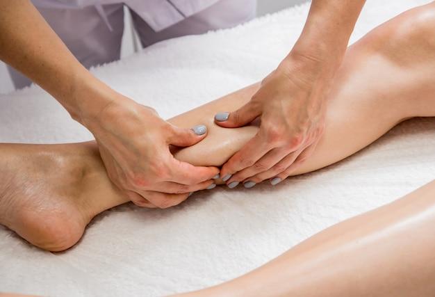 Mujer joven disfrutando de masaje de piernas con aceite en el salón de spa. cosmetología
