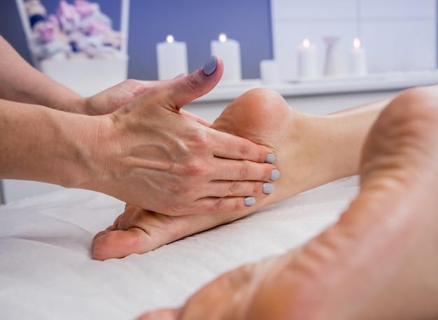 Mujer joven disfrutando de masaje de pies en el salón de spa. cosmetología