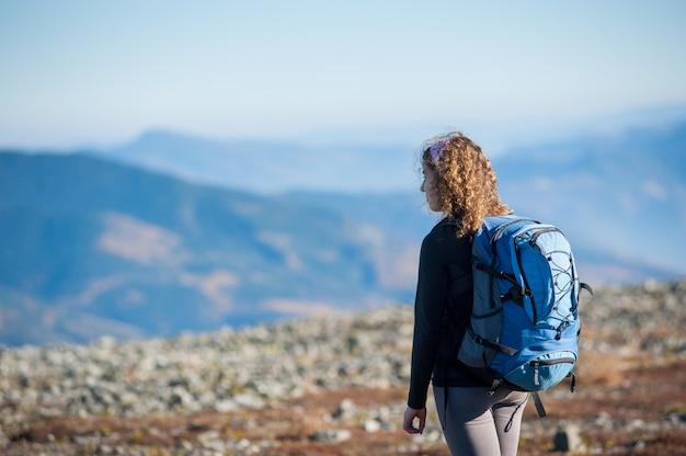 Mujer joven disfrutando de la naturaleza en viaje de mochilero en las montañas