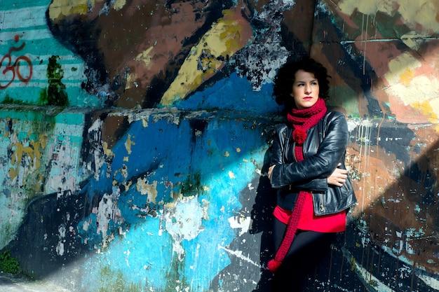 Mujer joven disfrutando del sol en la calle con pared de graffiti.