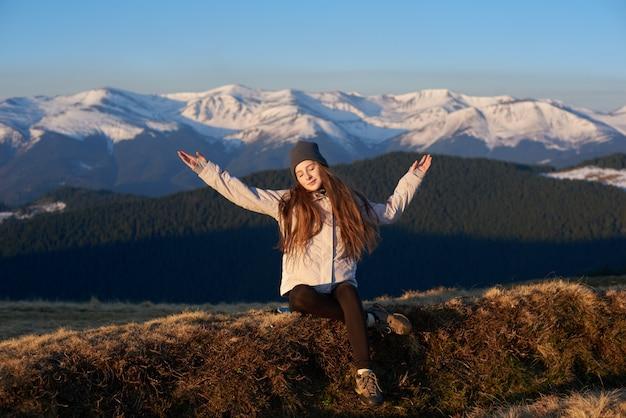 Mujer joven disfrutando del sol de la mañana en las montañas