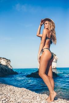 Mujer joven disfrutando del sol tomando el sol junto al mar turquesa perfecto