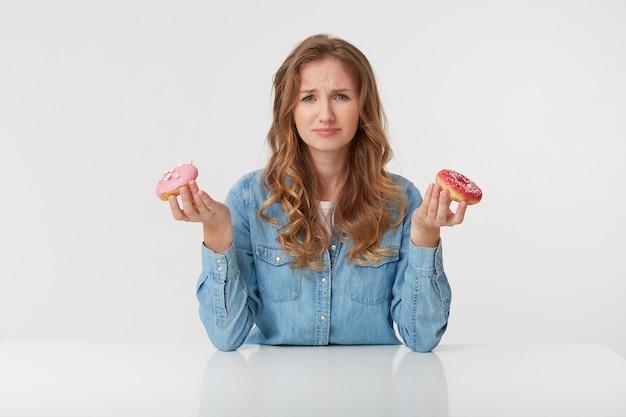 Mujer joven disgustada con largo cabello rubio ondulado, sentada en la mesa y sostiene donas en sus manos. fruncir el ceño, mirando con disgusto a la cámara aislada sobre fondo blanco.
