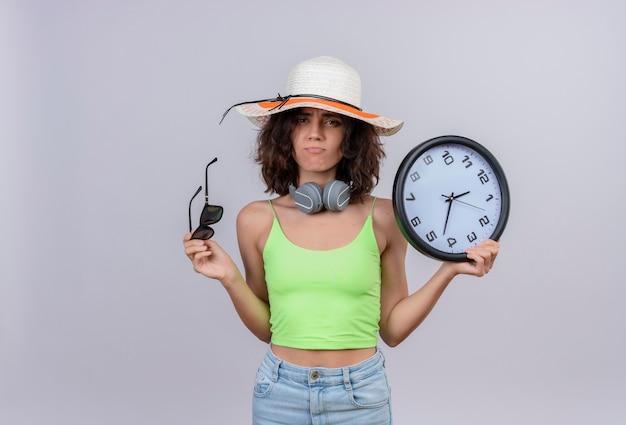 Una mujer joven disgustada con el pelo corto en verde crop top con sombrero para el sol sosteniendo gafas de sol y reloj de pared sobre un fondo blanco.